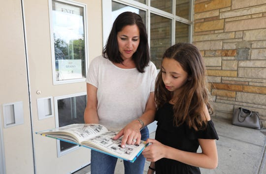 Lauren Rufo Stanco of Hawthorne shows her daughter Mia Stanco, 11, her school yearbook July 24, 2019 at Family School 32 in Yonkers, which Stanco attended till 7th grade. In an effort desegregate schools in 1986, Stanco was bused to junior high school outside her neighborhood.