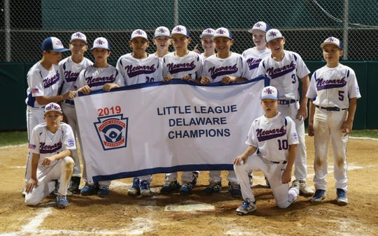 Newark National poses with the championship banner after beating Lower Sussex 5-2 to clinch the state Little League title in the major division Wednesday. The team moves on to represent Delaware in the Bristol, Conn. regional tournament.