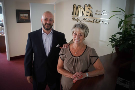 (left to right) Michael Rappucci, corporate operations, stands with his mother Cheryl Rappucci, who is the president of Mortgage Network Solutions, in the lobby of their Brandywine Hundred business. The mortgage company won second place in the small company category of The News Journal's Top Workplaces contest.