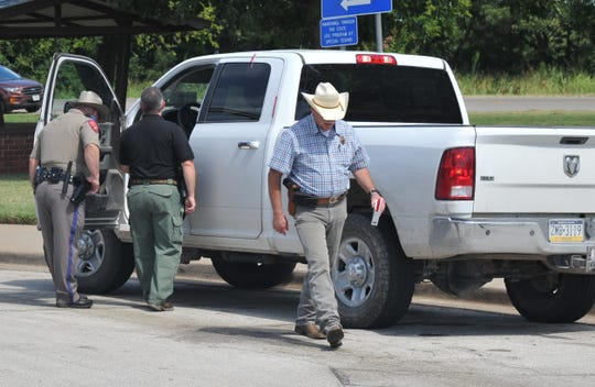 A DPS Trooper and Wichita County Sheriff's Office investigators search a vehicle that an alleged homicide suspect drove from Carlsbad, NM to a rest stop near Iowa Park, Thursday morning.