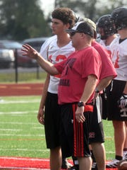 Crooksville assistant coach Greg Williams talks to quarterback Caden Miller during a 7-on-7 scrimmage against Lakewood on Wednesday. Miller is back in action after a 10-month layoff from knee surgery.