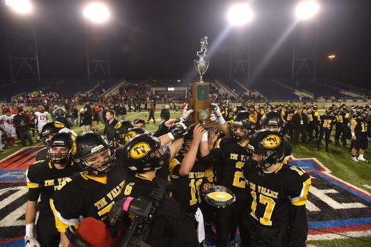 Tri-Valley holds its Division III state runner up trophy after falling to Trotwood Madison in Canton on Saturday.