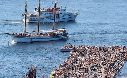 The bathing area at Sorenga is seen crowded with people while the cruise boats sail close to the dock in the capital's inner harbor pool in in Oslo on July 24, 2019.