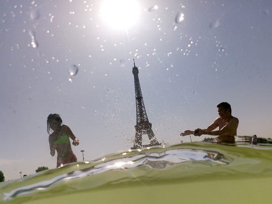 People cool off at the Trocadero Fountains next to the Eiffel Tower in Paris, on July 25, 2019.
