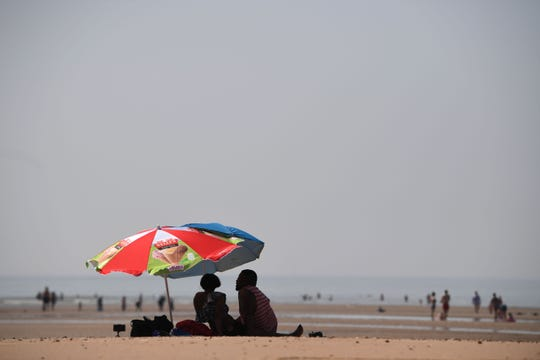 Beachcombers seek shelter under an umbrella by the sea on July 25, 2019 in Camber Sands, England.