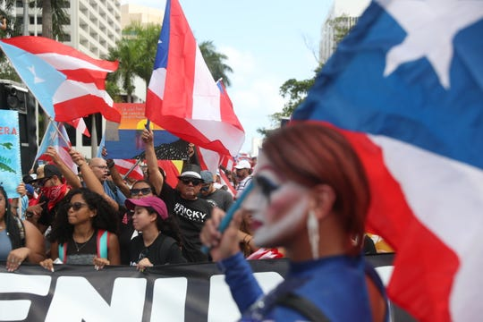 People march through the financial district as they celebrate the ouster of Ricardo Rossello, the Governor of Puerto Rico, on July 25, 2019 in Old San Juan, Puerto Rico.  After two weeks of protess Gov. Rosselló stepped down after a group chat was exposed that included misogynistic and homophobic comments.