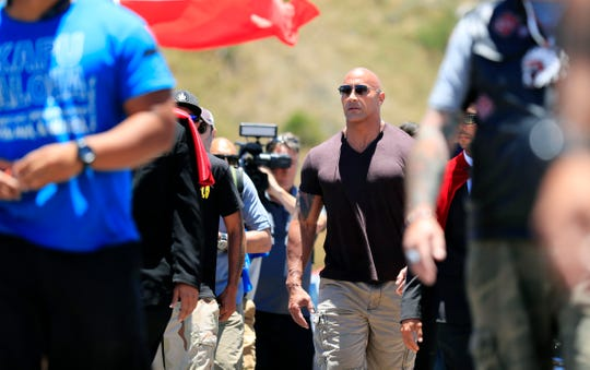 """Actor Dwayne """"The Rock"""" Johnson walks on Mauna Kea Access Road during a visit to the protest site against the TMT telescope on Wednesday, July 24, 2019, at the base of Mauna Kea on Hawaii Island."""