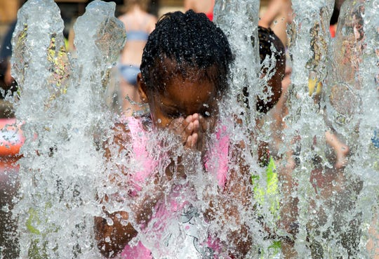 A girl cools off by standing in a park fountain in Antwerp, Belgium on July 25, 2019.