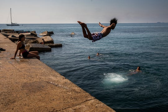 A boy jumps into the water at the beach in Barcelona, Spain on July 25, 2019.