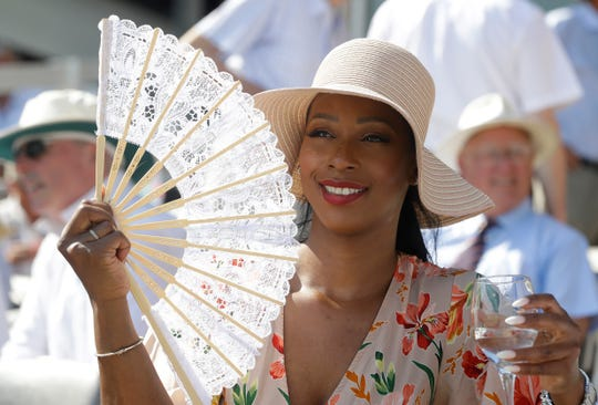 A spectator uses a fan to keep cool ahead of the second day of the test match between England and Ireland at Lord's cricket ground in London on July 25, 2019.
