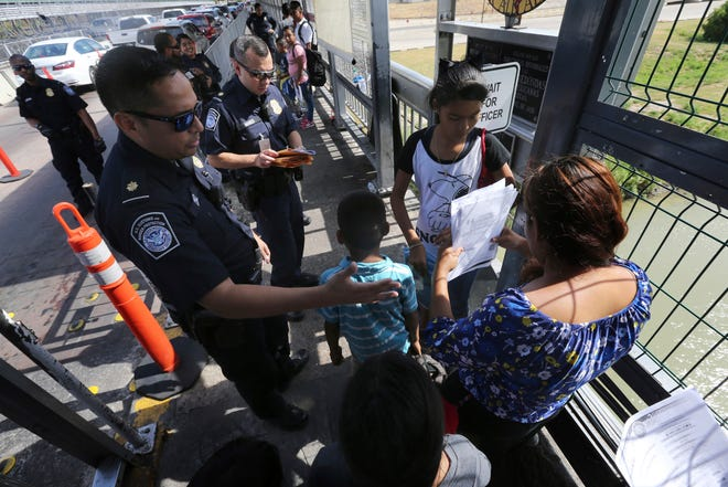 In this July 17, 2019, file photo, a United States Customs and Border Protection Officer checks the documents of migrants before being taken to apply for asylum in the United States, on International Bridge 1 in Nuevo Laredo, Mexico. On Wednesday, July 24, 2019, a federal judge in San Francisco blocked the Trump administration's asylum restrictions at the U.S.-Mexico border.
