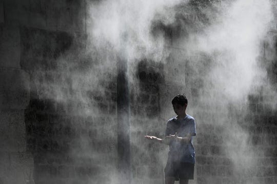 A boy cools off under a public water spray on the bank of the Seine river in Paris on July 25, 2019.