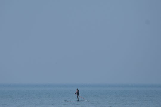 A paddler stands on a board in the sea at Camber Sands, England on July 25, 2019.