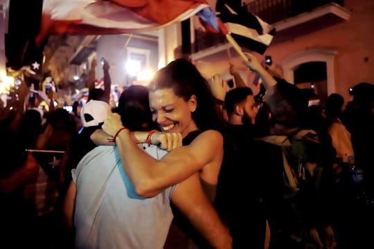 Dozens of people celebrate next to La Fortaleza after the resignation announcement of the Governor of Puerto Rico Ricardo Rossello.