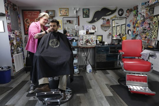 In Shear Chaos' new location, Thiago Pereira of Appleton gets a hair cut from Nicole Von Morris.