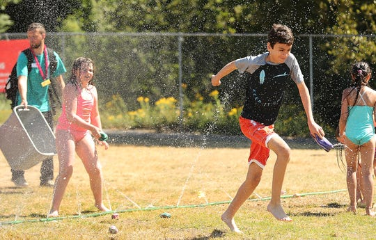 Gabe Pritchard dashes through the sprinklers running from a fellow camper tossing a soaked sponge in his direction as the campers cool off during Day Camp at the YMCA in Bremerton on Friday, July 26, 2019.