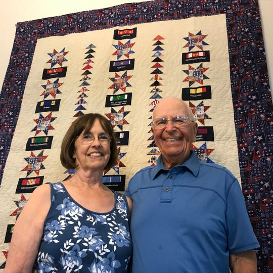 Eileen and Giles Norrington stand in front of a quilt bearing the images of awards bestowed on Giles, a former POW. They include two Bronze Stars, two Purple Hearts, three Legion of Merit medals and the Navy Commendation medal.