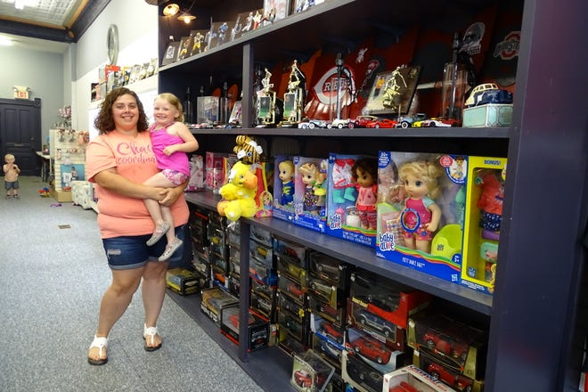 Angela Lewis holds daughter Tali Lewis, 4, at Hidden Treasures in Galion.