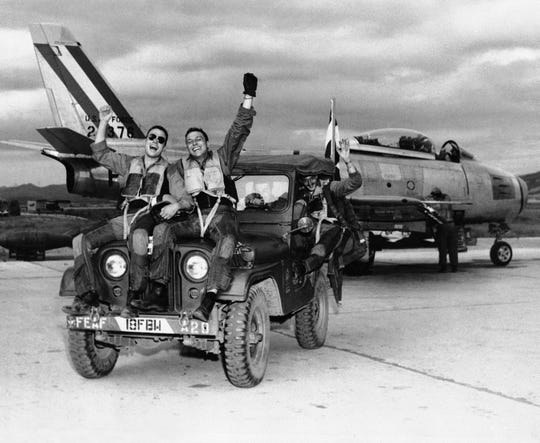 Members of the 18th Fighter Bomber wing cheer at news of the Korean armistice in July 1953 as they return from a combat mission.