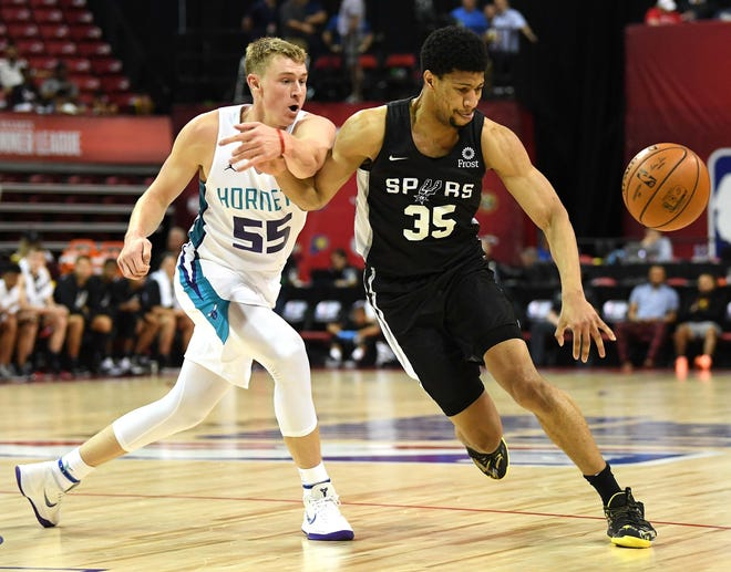 Charlotte Hornets guard JP Macura (55) tips the ball away from San Antonio Spurs forward Jordan Barnett (35) during the first half of an NBA Summer League game at Thomas & Mack Center on July 7.