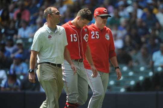 Jul 24, 2019; Milwaukee, WI, USA; Cincinnati Reds center fielder Nick Senzel (15) center walks off the field with trainer Steve Baumann and Cincinnati Reds manager David Bell (25) after singling to first base in the first inning against the Milwaukee Brewers at Miller Park. Mandatory Credit: Michael McLoone-USA TODAY Sports