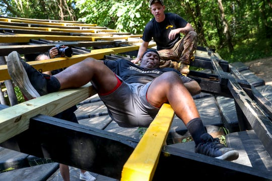 "John ""Big John"" Whiteside stretches over bars while navigating his way to the end of an obstacle at the Air Assault School obstacle course in Fort Campbell, KY., on Thursday, July 25, 2019."