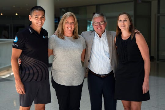 Matt Zepeda, owner of Zoom Performance and triathlon coach; Jen Schulte, Des Moines' director of government relations; Greg Edwards, CEO of Catch Des Moines; and Trina Flack, vice president of Catch Des Moines' sales pose for a portrait at Capital Square on July 26, 2019. Not pictured: West Des Moines City Manager Lucinda Stephenson and TJ Tollakson, professional triathlete.