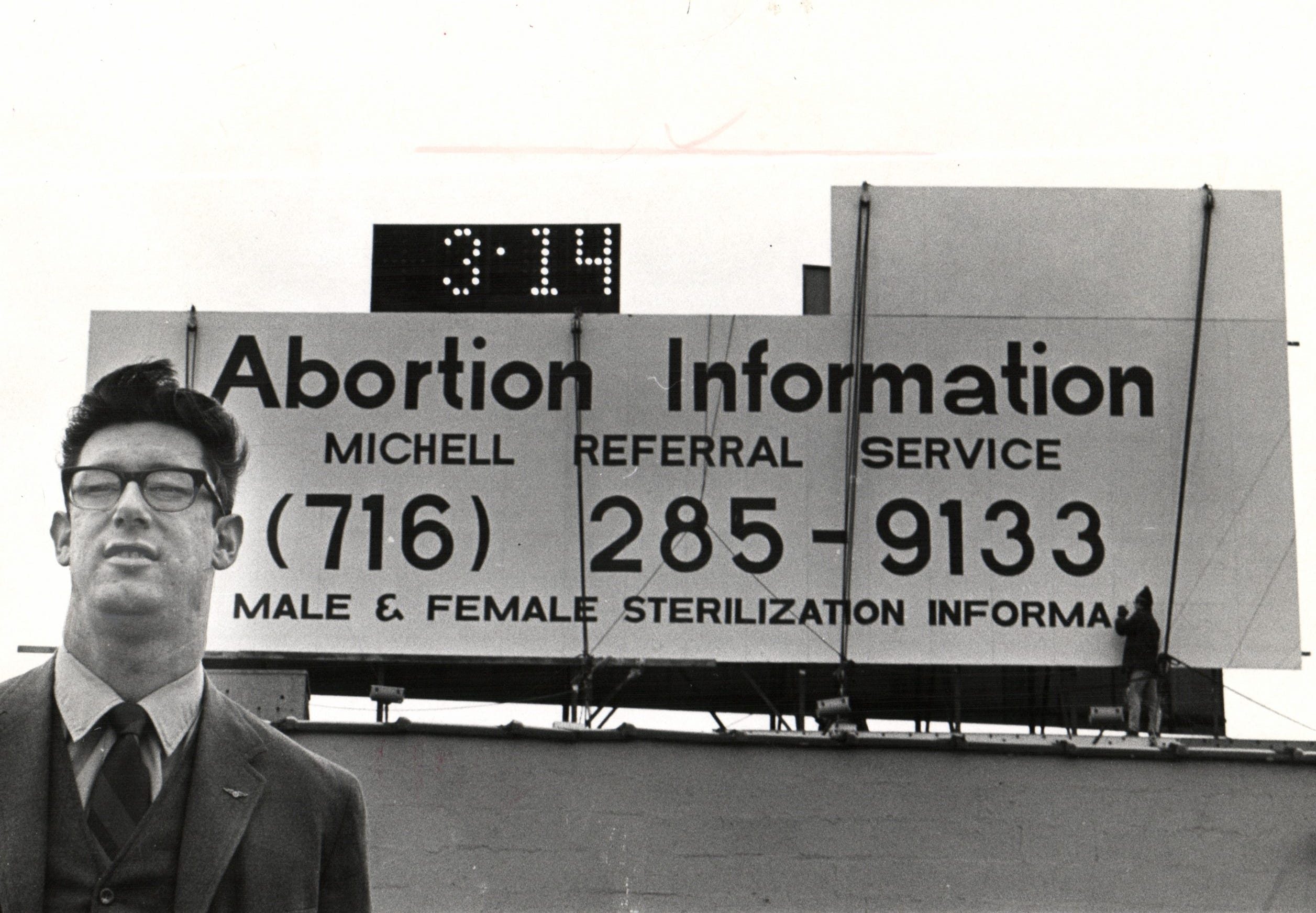 Martin Mitchell stands before a billboard advertising his abortion service in 1970.