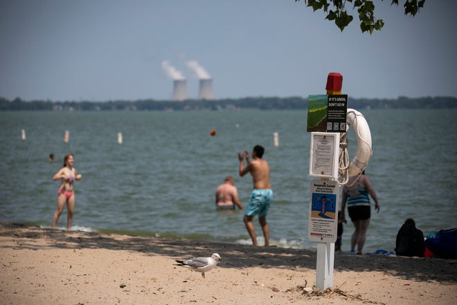 Beachgoers enjoy Lake Erie despite a yellow warning flag indicating dangerous conditions at Sterling State Park in Monroe Friday, July 26, 2019.
