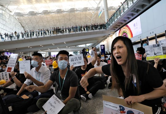 Demonstrators shout slogans during a protest at Hong Kong International Airport, Friday, July 26, 2019.