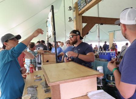 Jordan Frazier talks beer with a visitor to the Ore Dock Brewing stand at the Michigan Brewers Guild Summer Beer Festival in Riverside Park in Ypsilanti.