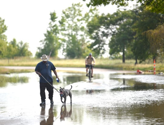 Clifton Webb, left, of Detroit, walks his three-year-old male Blue Nose Pitbull named, 'Baby,' as Chuck Stewart, right, of Bayonne, NJ rides his bike through flood water along The Strand on Belle Isle, in Detroit. Recent flooding on the island came close to swamping an electrical substation that provides power to the entire park.
