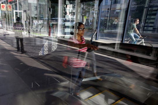 A passer-by, center, uses an escalator while emerging from a subway station, in Boston's Seaport district.
