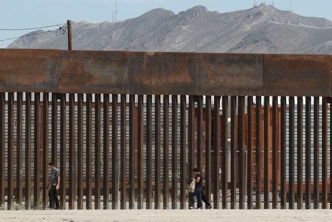 Three migrants who had managed to evade the Mexican National Guard and cross the Rio Grande onto U.S. territory walk along a border wall set back from the geographical border, in El Paso, Texas, as seen from Ciudad Juarez, Mexico, Wednesday, July 17, 2019.