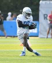 Lions running back Kerryon Johnson reaches back for a reception during drills.