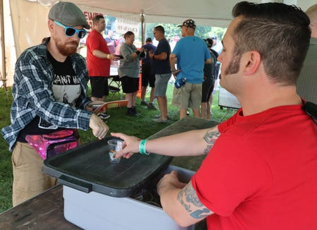 Kyle Kipp, 41, of Ypsilanti, hands a sample cup and tokens to a beer festival attendee Friday. Kipp said he lives in the neighborhood volunteers every year.