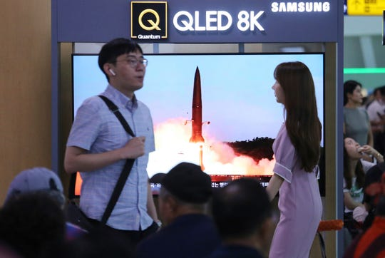 People watch a TV showing an image of North Korea's missile launch during a news program at the Seoul Railway Station in Seoul, South Korea, Friday, July 26, 2019.