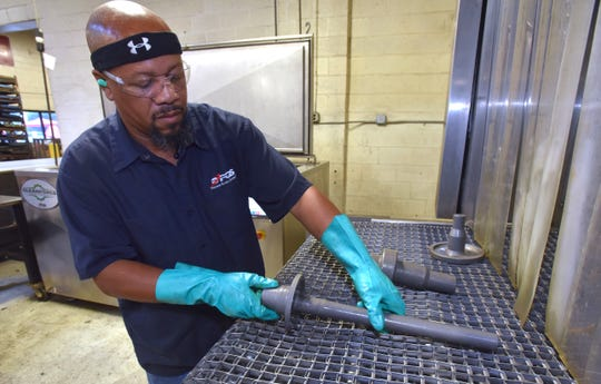 Line leader Larry Johnson of Detroit puts de-rusted components into an automated, high-pressure machine that washes, rinses and dries the components.