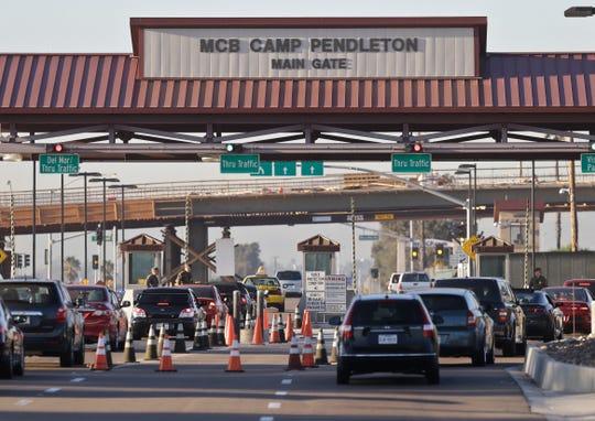 In this Nov. 13, 2013 file photo vehicles file through the main gate of Camp Pendleton Marine Base at Camp Pendleton, Calif.