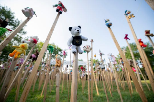 Dozens of dolls and toys on wooden stakes stand as part of an installation outside the Birmingham Temple Congregation for Humanistic Judaism, in Farmington Hills, July 26, 2019. Elaine Roseborough, the exhibit's creator, conceived the work as a response to President Donald Trump's administration's actions separating migrant children from their families at the United States' border with Mexico.