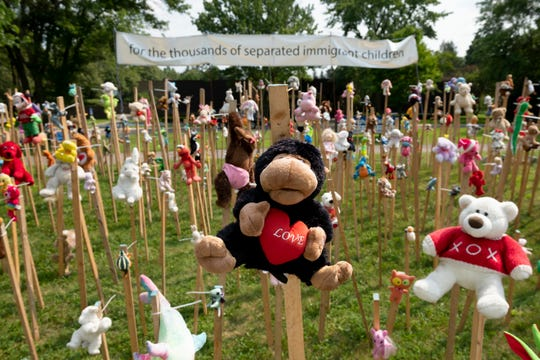 Dozens of dolls and toys on wooden stakes stand as part of an installation outside the Birmingham Temple Congregation for Humanistic Judaism, in Farmington Hills. Elaine Roseborough, the exhibit's creator, conceived the work as a response to the Trump administration's actions separating migrant children from their families at the United States' border with Mexico.