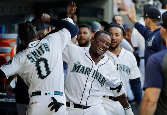 Seattle Mariners' Tim Beckham, right, celebrates in the dugout with Mallex Smith (0) after Beckham hit a grand slam during the third inning.