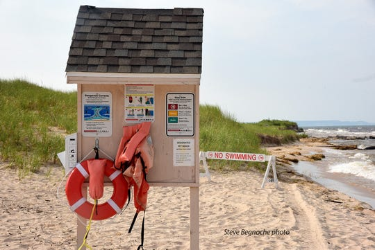 An informational kiosk with water rescue equipment is seen near the Big Sable River outlet in Ludington.