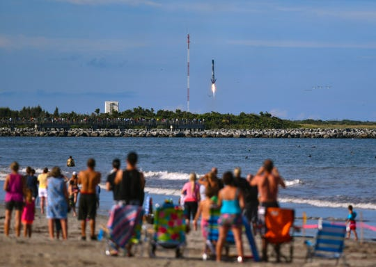 People on the beach north of Cherie Down Park in Cape Canaveral, Fla., watch and photograph the landing of the first stage of the Falcon 9 SpaceX rocket after a successful launch to resupply the International Space Station, Thursday, July 25, 2019.