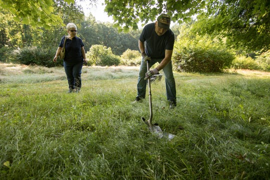 In this July 24, 2019, photo a couple look for the burial plot of their Yorkshire terrier dog Henry at Heavenly Acres Pet Cemetery in the hopes of exhuming the dog's remains and having them cremated in Genoa Township, Mich. Some owners of pets buried at a shuttered Michigan pet cemetery that houses remains of an estimated 74,000 animals are getting a last chance to exhume the remains of the animals. (Gillis Benedict/Livingston County Daily Press & Argus via AP)