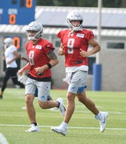 Lions quarterbacks Tom Savage and Matthew Stafford jog to the next drill during practice.