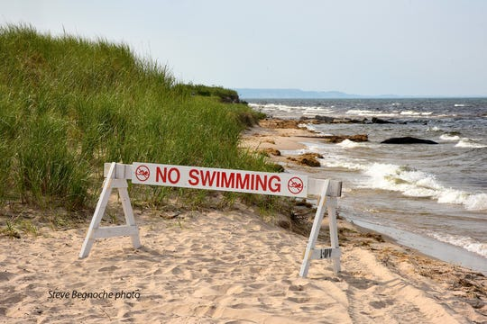 A no swimming sign is placed near the outlet of the Big Sable River in Ludington.
