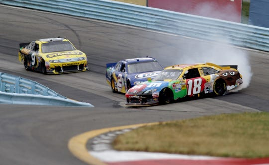 Kyle Busch (18) is involved in an incident ahead of Brad Keselowski (2) and Marcos Ambrose during the NASCAR Cup Series race at Watkins Glen International in 2012.