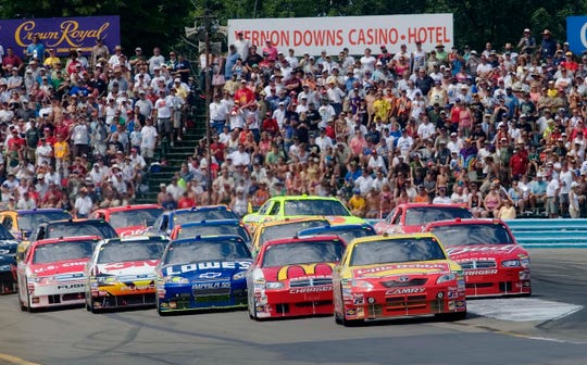 Marcos Ambrose leads the pack out of Turn 1 driving the 2009 Cup Series race at Watkins Glen International.
