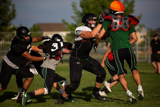 Fossil Ridge High School junior offensive lineman Trey Zuhn knocks a teammate off his spot while participating in a drill during practice on Thursday, July 25, 2019, in Fort Collins, Colo.